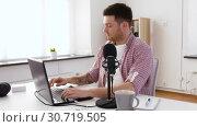 Купить «young man with laptop and microphone at home», видеоролик № 30719505, снято 2 мая 2019 г. (c) Syda Productions / Фотобанк Лори