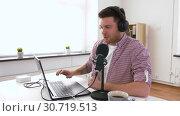 Купить «man in headphones with laptop speaks to microphone», видеоролик № 30719513, снято 2 мая 2019 г. (c) Syda Productions / Фотобанк Лори