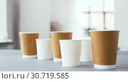 Купить «various disposable paper cups for hot drinks», видеоролик № 30719585, снято 5 мая 2019 г. (c) Syda Productions / Фотобанк Лори
