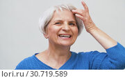 Купить «portrait of smiling senior woman touching her hair», видеоролик № 30719589, снято 5 мая 2019 г. (c) Syda Productions / Фотобанк Лори