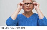 Купить «portrait of senior woman putting her glasses on», видеоролик № 30719593, снято 5 мая 2019 г. (c) Syda Productions / Фотобанк Лори