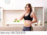 Купить «Young beautiful girl with tape meter in dieting concept», фото № 30723513, снято 17 декабря 2018 г. (c) Elnur / Фотобанк Лори
