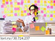 Купить «Young employee in conflicting priorities concept», фото № 30724237, снято 16 октября 2018 г. (c) Elnur / Фотобанк Лори