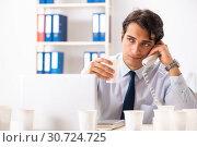 Купить «Young employee addicted to coffee», фото № 30724725, снято 26 июля 2018 г. (c) Elnur / Фотобанк Лори