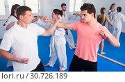 Купить «Adults training at karate class», фото № 30726189, снято 8 апреля 2017 г. (c) Яков Филимонов / Фотобанк Лори
