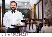 Купить «Professional waiter holding serving tray for restaurant guests», фото № 30726281, снято 11 декабря 2017 г. (c) Яков Филимонов / Фотобанк Лори