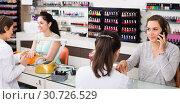 Купить «smiling woman getting manicure in beauty salon and talking on phone», фото № 30726529, снято 28 апреля 2017 г. (c) Яков Филимонов / Фотобанк Лори