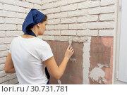 Уставшая девушка выполняет работы по имитации кирпичной кладки на стене. Стоковое фото, фотограф Иванов Алексей / Фотобанк Лори