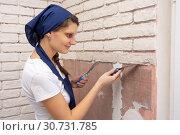 Девушка штукатур формирует из штукатурной массы кирпичи на стене. Стоковое фото, фотограф Иванов Алексей / Фотобанк Лори
