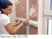 Девушка разлиновывает стену для имитации кирпичной кладки. Стоковое фото, фотограф Иванов Алексей / Фотобанк Лори