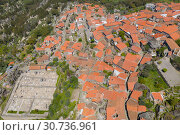 Купить «Aerial view of small rural village with red roofs located in mountains. Top View of Monsanto village in central Portugal», фото № 30736961, снято 27 апреля 2019 г. (c) Кирилл Трифонов / Фотобанк Лори