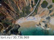 Купить «Aerial view of a sandy beach line full of bathers and colorful umbrellas on Do Camilo beach in Lacos, Algarve, Portugal», фото № 30736969, снято 29 апреля 2019 г. (c) Кирилл Трифонов / Фотобанк Лори