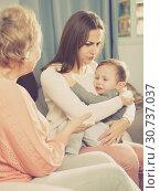 Купить «Adult female with her mother are having disagreements for parenting child», фото № 30737037, снято 15 февраля 2018 г. (c) Яков Филимонов / Фотобанк Лори
