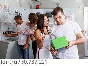 Купить «Young friends inspecting battery charger», фото № 30737221, снято 8 октября 2018 г. (c) Яков Филимонов / Фотобанк Лори