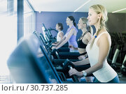 Купить «Slender athletic girls running on treadmill in fitness club», фото № 30737285, снято 26 июля 2017 г. (c) Яков Филимонов / Фотобанк Лори
