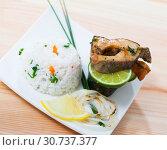 Купить «Tasty baked trout steaks, served with rice and lemon at white plate», фото № 30737377, снято 23 июля 2019 г. (c) Яков Филимонов / Фотобанк Лори