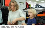 Купить «Mother and son try on sports shoes in a sports store», видеоролик № 30737581, снято 19 апреля 2019 г. (c) Антон Гвоздиков / Фотобанк Лори