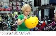 Купить «Boy chooses bike helmet in the shop», видеоролик № 30737589, снято 14 декабря 2019 г. (c) Антон Гвоздиков / Фотобанк Лори