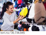 Female customer examining knit caps in sports store. Стоковое фото, фотограф Яков Филимонов / Фотобанк Лори