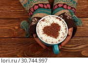 Купить «Close up two woman hands hold and hug big full cup of latte cappuccino coffee with heart shaped chocolate on milk froth over brown wooden table, elevated top view, directly above», фото № 30744997, снято 11 ноября 2017 г. (c) easy Fotostock / Фотобанк Лори