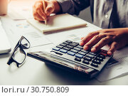 Купить «Businessmen are using a calculator to calculate the income of the business.», фото № 30750809, снято 6 июня 2018 г. (c) easy Fotostock / Фотобанк Лори