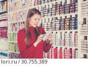 Купить «Ordinary woman is choosing new hair dye», фото № 30755389, снято 22 марта 2018 г. (c) Яков Филимонов / Фотобанк Лори