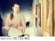 Купить «Glad girl holding guide book in museum», фото № 30755485, снято 18 ноября 2017 г. (c) Яков Филимонов / Фотобанк Лори