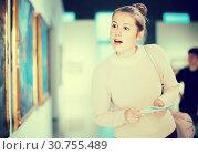 Купить «Pretty woman holding guide book in museum», фото № 30755489, снято 18 ноября 2017 г. (c) Яков Филимонов / Фотобанк Лори