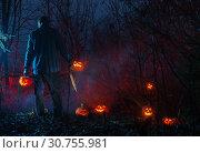 Купить «scary man in night forest is cutting Halloween pumpkins», фото № 30755981, снято 10 ноября 2018 г. (c) Майя Крученкова / Фотобанк Лори