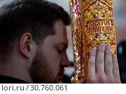 Православный священнослужитель держит Святое Евангелие во время службы в храме (2019 год). Редакционное фото, фотограф Николай Винокуров / Фотобанк Лори