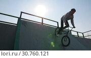 Купить «A professional BMX rider in grey hoodie riding down on the ramp in the skatepark», видеоролик № 30760121, снято 20 июня 2019 г. (c) Константин Шишкин / Фотобанк Лори