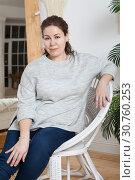 Купить «Calm woman sitting in rattan armchair in domestic room, looking at camera», фото № 30760253, снято 17 февраля 2019 г. (c) Кекяляйнен Андрей / Фотобанк Лори