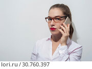 Купить «Attractive caucasian woman in stylish eyeglasses holding smartphone», фото № 30760397, снято 19 октября 2017 г. (c) Pavel Biryukov / Фотобанк Лори