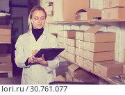 Купить «Female worker transporting cart cardboard cases», фото № 30761077, снято 22 апреля 2017 г. (c) Яков Филимонов / Фотобанк Лори