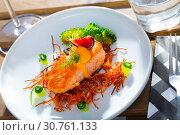 Купить «Steak of fried salmon with smoked carrots, broccoli, cucumbers and fig on plate», фото № 30761133, снято 14 октября 2019 г. (c) Яков Филимонов / Фотобанк Лори