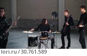 Купить «A rock group having a repetition. A man with long hair sets the rhythm», видеоролик № 30761589, снято 6 июля 2020 г. (c) Константин Шишкин / Фотобанк Лори