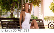 Luxurious beautiful slim blonde in a sexy white dress and high-heeled sandals sits on a bench in the park. Стоковое фото, фотограф katalinks / Фотобанк Лори