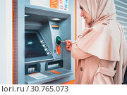 Купить «Beautiful Muslim woman in headscarf and fashionable modern trendy clothes pulls in debit card at an ATM. ATM cash terminal with display.», фото № 30765073, снято 14 апреля 2019 г. (c) easy Fotostock / Фотобанк Лори