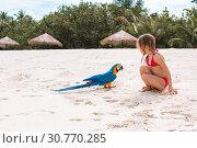 Купить «Adorable little girl at beach with colorful parrot», фото № 30770285, снято 28 марта 2015 г. (c) Дмитрий Травников / Фотобанк Лори