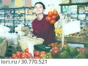 Купить «Portrait of joyous young female customer selecting tomatoes in grocery», фото № 30770521, снято 1 марта 2017 г. (c) Яков Филимонов / Фотобанк Лори