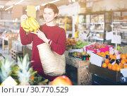 Купить «Portrait of happy young customer selecting bananas in grocery», фото № 30770529, снято 1 марта 2017 г. (c) Яков Филимонов / Фотобанк Лори