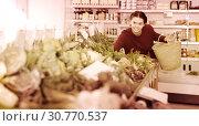 Купить «Young female customer in grocery», фото № 30770537, снято 1 марта 2017 г. (c) Яков Филимонов / Фотобанк Лори