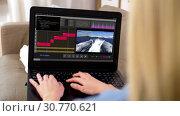 Купить «woman with video editor program on laptop at home», видеоролик № 30770621, снято 24 января 2020 г. (c) Syda Productions / Фотобанк Лори