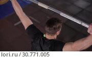 Купить «Top View Of A Young Unidentified Man Raises The Heavy Barbell», видеоролик № 30771005, снято 12 июля 2020 г. (c) Pavel Biryukov / Фотобанк Лори