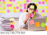 Купить «Young employee in conflicting priorities concept», фото № 30779561, снято 16 октября 2018 г. (c) Elnur / Фотобанк Лори