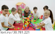 Купить «Happy kids and female teacher playing together with colorful toy building blocks in classroom at elementary school», видеоролик № 30781221, снято 18 декабря 2018 г. (c) Яков Филимонов / Фотобанк Лори