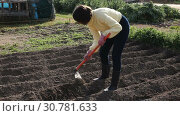Купить «Young woman farmer working with hoe in vegetable garden, hoeing the soil», видеоролик № 30781633, снято 26 февраля 2019 г. (c) Яков Филимонов / Фотобанк Лори