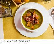 Купить «Top view of creamy zucchini soup with croutons and jamon», фото № 30789297, снято 18 июля 2019 г. (c) Яков Филимонов / Фотобанк Лори