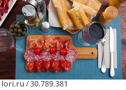 Купить «Spanish tasty meal slicing sausages and jamon with tomatoes, close up», фото № 30789381, снято 17 июля 2019 г. (c) Яков Филимонов / Фотобанк Лори
