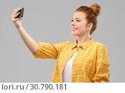 Купить «redhead teenage girl taking selfie by smartphone», фото № 30790181, снято 28 февраля 2019 г. (c) Syda Productions / Фотобанк Лори